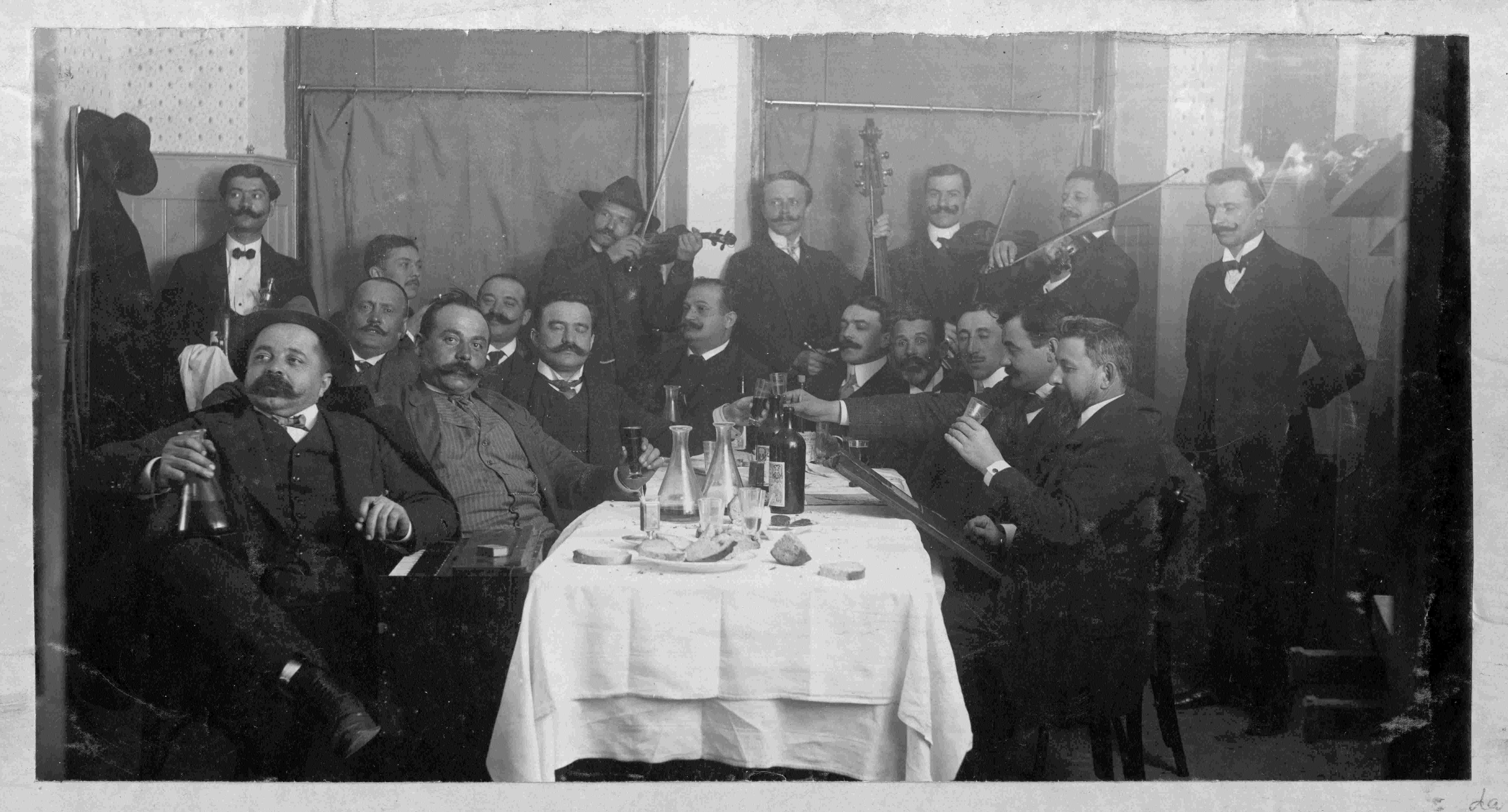 """Petrović (violinist with the hat) conducts the musical band """"Suz"""" during a tavern party. (SASA Archive, 14197/1)"""